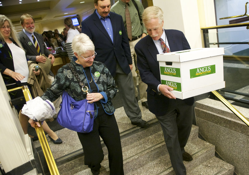 Former Gov. Angus King carries a box of signature-filled petitions to the Cross Building in Augusta on Tuesday morning to get himself on the ballot in this fall's race to replace Sen. Olympia Snowe, R-Maine, who is retiring.