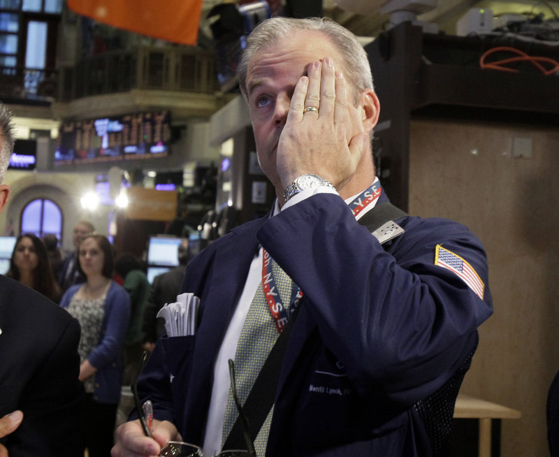 Trader David O'Day works Wednesday on the New York Stock Exchange floor. The Dow Jones closed down 161 points.
