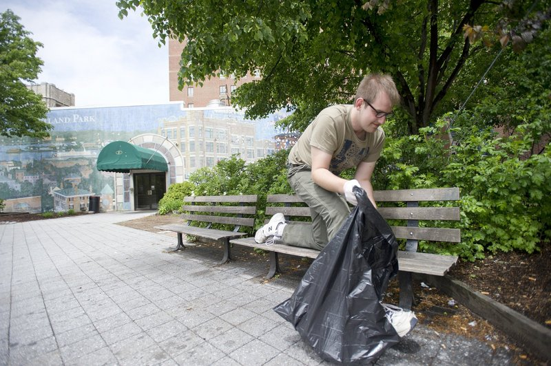 Jake Lowry gathers trash last week in Congress Square during a cleanup organized by Occupy Maine. The Eastland Park Hotel's owners want to build a ballroom there, but Occupy Maine wants to preserve the space for public assembly.