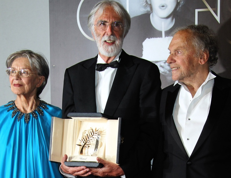 """Director Michael Haneke, center, poses Sunday with the Palme d'Or for """"Amour,"""" flanked by actors Emmanuelle Riva and Jean-Louis Trintignant."""