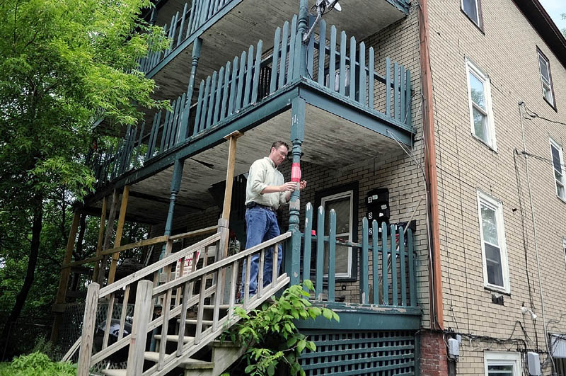 UNSAFE CONDITIONS: Augusta code enforcement officer Rob Overton tapes a notice on the deck at 11 State Street that wooden stairs and deck entrance to three apartments in the building is unsafe. Tenants in the units were ordered to relocate.
