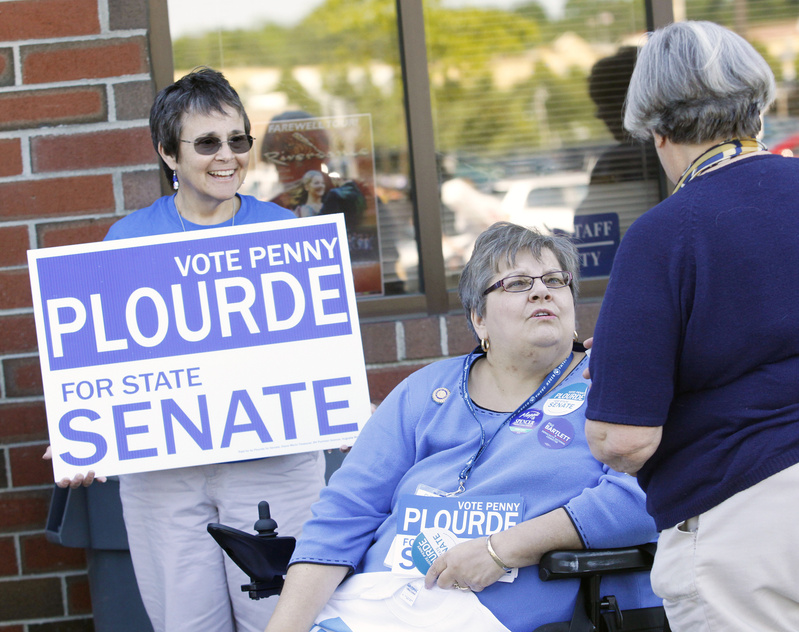 Penny Plourde, who is running for state Senate, and volunteer Donna Dachs of Augusta, left, greet people outside the Augusta Civic Center Friday.