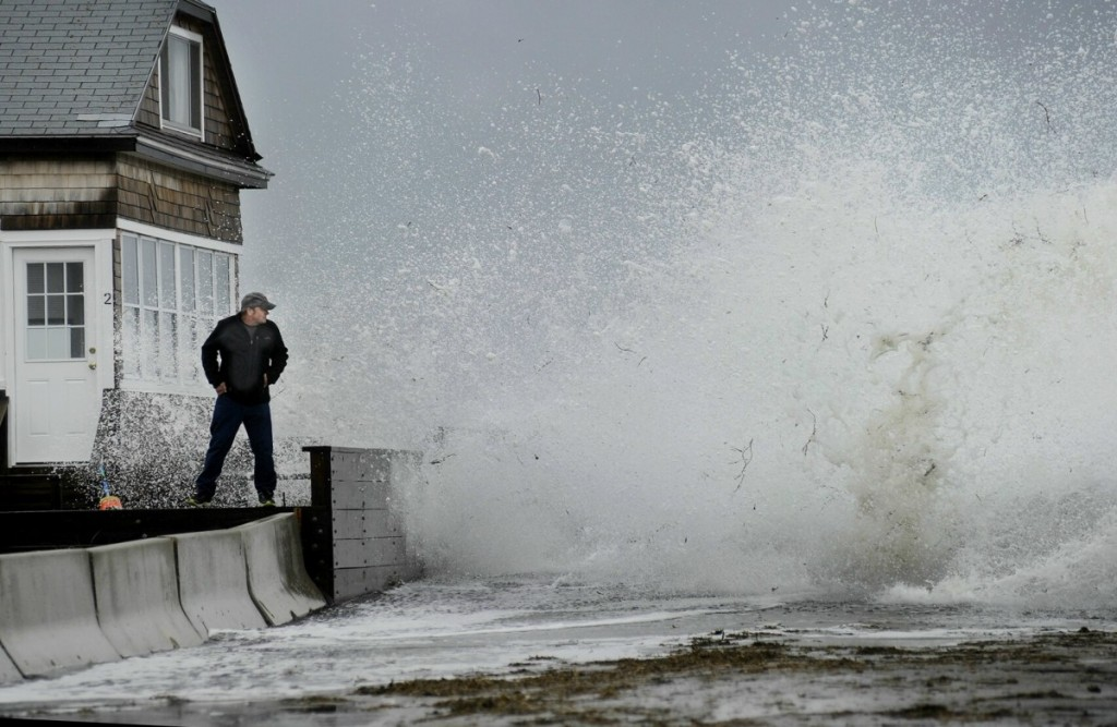 Staff Photo by Shawn Patrick Ouellette: Bernie Malouin watches a large wave crash over Eastern Ave. at Camp Ellis in Saco from a wall in front of his cottage Monday, June 4, 2012. The wave soaked Malouin who continued to monitor the high tide under the cover of his cottage after changing into some dry clothes.
