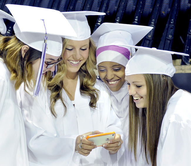 Grads Alexis Wyman, Victoria Adams, Samsam Mohamed and Katrina Pooler look at a photo just taken of them prior to the Deering High School commencement today.