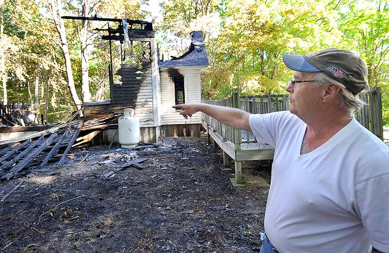 Steve Thibeault, the son of the former pastor, points to damaged remains of the church. Pastor Greg Martin said the building was insured, but that the loss of such a historic building and its memories will be hard to overcome.