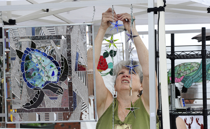 Stained-glass artist Peggy Pulling from Gorham sets up her display at the sidewalk art show today highlighting Saco's 250th Anniversary Celebration.