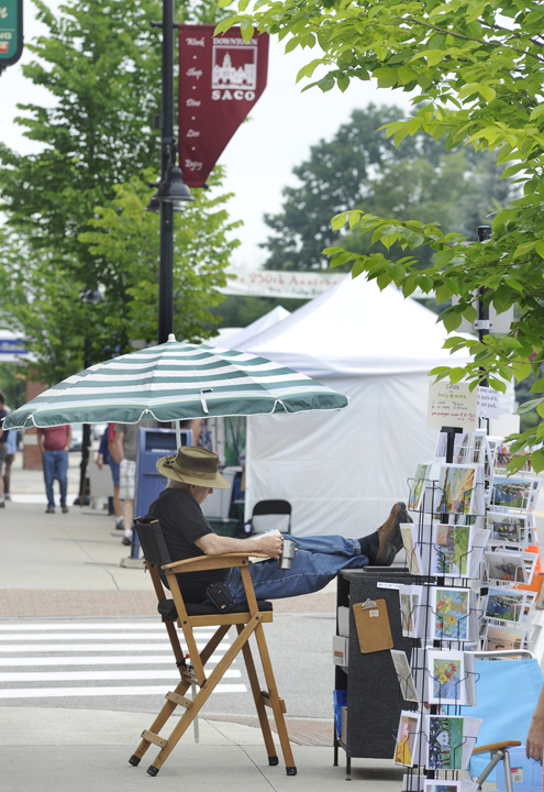 Artist Joseph Barnett from Kennebunk relaxes after setting up his display at Saco's 250th Anniversary Celebration sidewalk art show.
