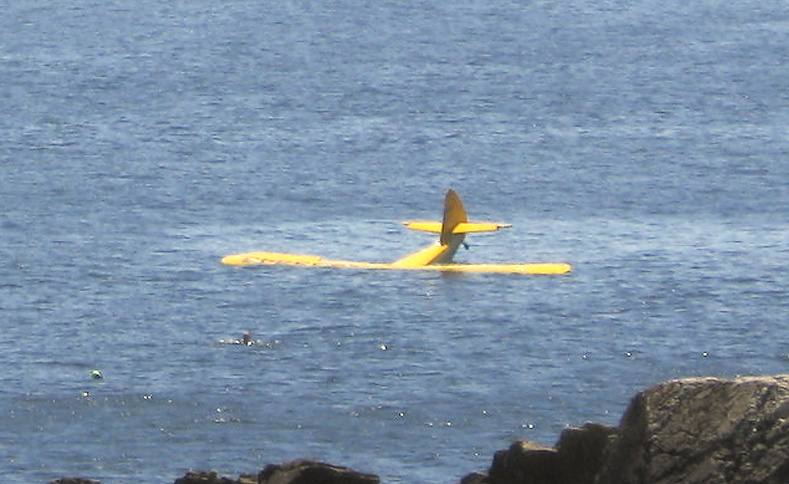 Dr. Louis Hanson's 1946 Stinson Voyager sinks off Fort Williams Park in Cape Elizabeth on Sunday shortly after crashing into the ocean. Hanson, of Durham, can be seen in the water in front of the plane before he lost consciousness.
