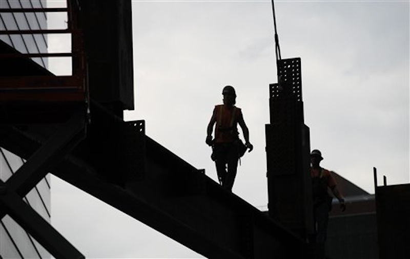 An ironworker walks a beam at Three World Trade Center, Monday, June 25, 2012 in New York. The 72-floor, 977-foot tower is scheduled to open late next year. It's expected to be the first tower completed on the 16-acre site since the 9/11 attacks. (AP Photo/Mark Lennihan) Silverstein;9/11;Sept 11;ground zero