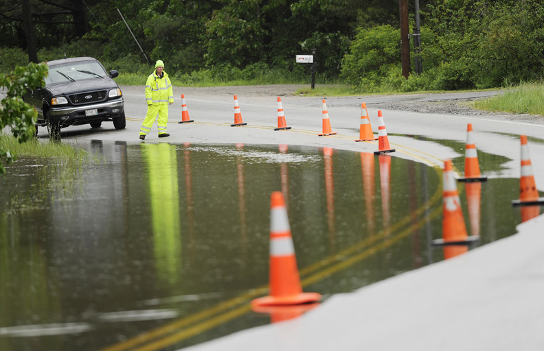 Rick Higgins, a Scarborough employee, keeps tabs on the rising water on Gorham Road in Scarborough on Sunday. Water from the nearby Nonesuch River was overtaking the road due to the heavy rain.