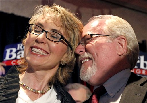 Democratic candidate Ron Barber celebrates his victory with former Rep. Gabrielle Giffords on Tuesday. Barber, Giffords' former district director, won a special election for the seat Giffords left in January to focus on her recovery from a gunshot wound.