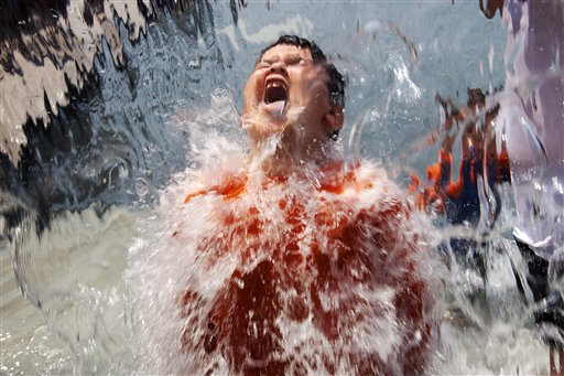 Lucas Olivo, 6, of Cheverly, Md., opens his mouth wide while running through a wall of water at Yards Park in Washington, D.C., today.