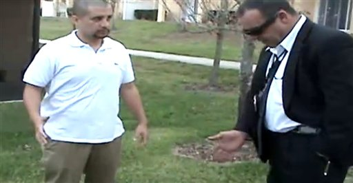 In this image from a Sanford Police video posted on a website called gzlegalcase.com by George Zimmerman's defense team, Zimmerman speaks to an unidentified investigator at the scene of Trayvon Martin's fatal shooting a day later, giving police a blow-by-blow account of his fight with the teen.