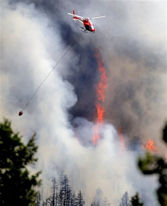 A firefighting helicopter flies above the Flagstaff fire on Tuesday, June 26, 2012 west of Boulder, Colo. Colorado has endured nearly a week of 100-plus-degree days and low humidity, sapping moisture from timber and grass, creating a devastating formula for volatile wildfires across the state and punishing conditions for firefighters. (AP Photo/The Boulder Daily Camera, Jeremy Papasso)