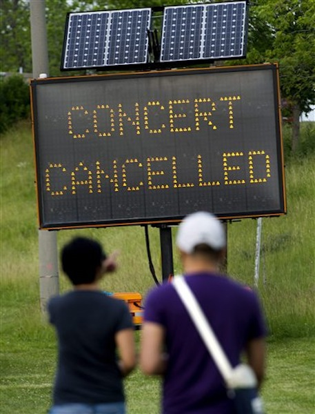 People read a sign informing of the cancellation of a Radiohead concert after a stage collapsed at Downsview Park in Toronto on Saturday, June 16, 2012. Toronto paramedics say one person is dead and another is seriously hurt after the stage collapsed while setting up for a Radiohead concert. They say two other people were injured and are being assessed. (AP Photo/The Canadian Press, Nathan Denette) injury;accident;bandage;bleeding;Canada;Canadian;care;hurt;injure;injured;internal;medical;medicine;sore;wound;wounded;health;festivals;art;arts;celebration;Ent;entertain;entertainers;entertaining;entertainment;event;events;festival;music;musician;performer;concert;artistic;band;live;performance;performing;play;playing;show;stage;general;entertainer;death;construct