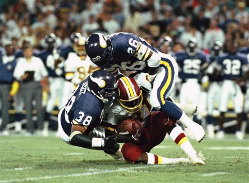 In this Aug. 29, 1992, file photo, Minnesota Vikings' Todd Scott (38) and Audrey McMillan (26) bring down Washington Redskins wide receiver Art Monk during an NFL football exhibition game in Washington. More than 60 former NFL players have filed a lawsuit in Los Angeles, joining hundreds of others who claim pro football didn't properly protect its players from concussions. Monk, the lead plaintiff, played for the Redskins from 1980 to 1993, and says in the lawsuit filed last week that he suffered multiple concussions in that time.