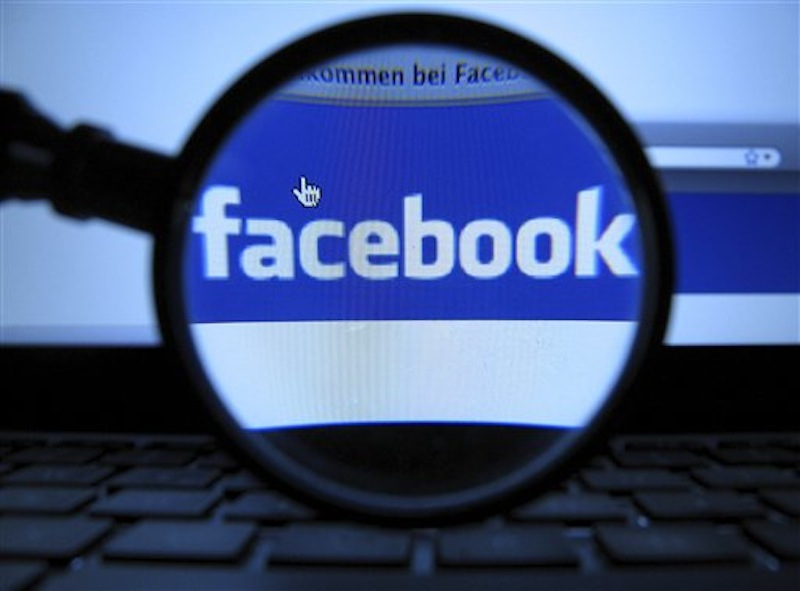In this Oct. 10, 2011 file photo, a magnifying glass is posed over a monitor displaying a Facebook page in Munich. Facebook is paying $10 million to settle a lawsuit over ads that it called sponsored stories. (AP Photo/dapd, Joerg Koch) T2012051103645