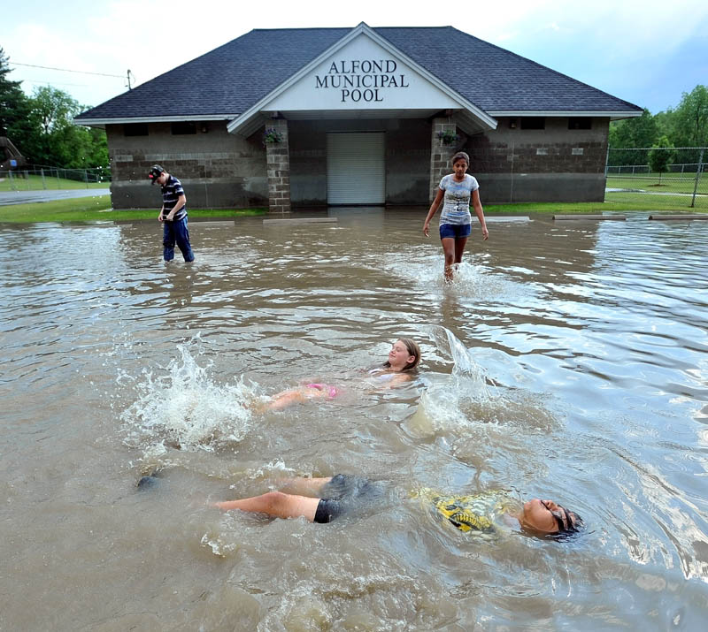 Zack Taylor, 13, foreground bottom and Caelie Burnham,12, second from bottom, float on their backs in the flood waters in the Alfond Municipal Pool on North Street in Waterville. Brandon Brown-Exner, 14, back left, and Nakia Accilien, 12, back right, walk to their friends.