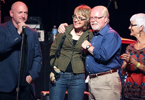 Mark Kelly, from left, former congresswoman Gabrielle Giffords, Ron Barber and Nancy Barber gather during a get-out-the-vote rally at the Rialto Theater in downtown Tucson, Ariz., on Saturday.