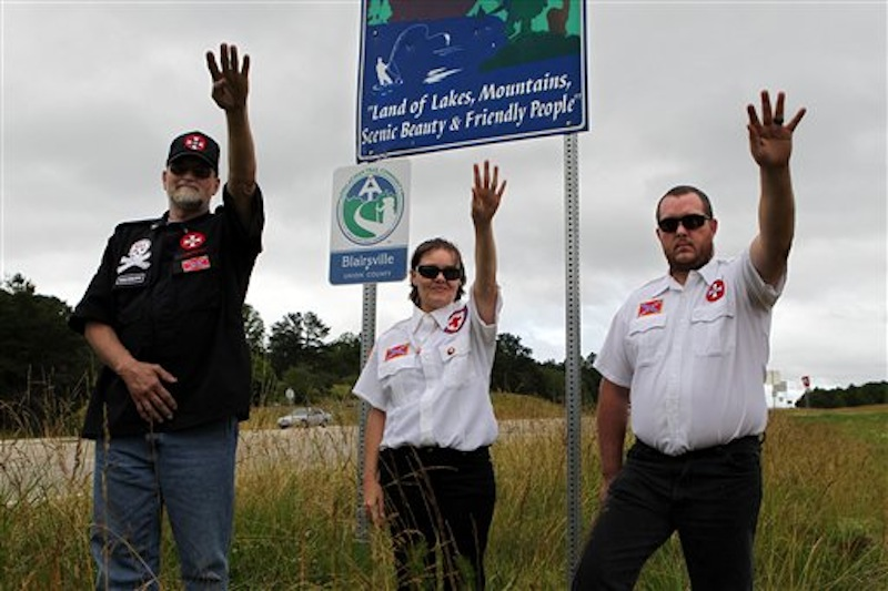 From left, Knighthawk, April Hanson and her husband Harley Hanson, members of the International Keystone Knights Realm of Georgia, perform a traditional Klan salute along the portion of highway they want to adopt allowing them to put up a sign and do litter removal near Blairsville, Ga., Sunday, June 10, 2012. The Ku Klux Klan group wants to join Georgia's