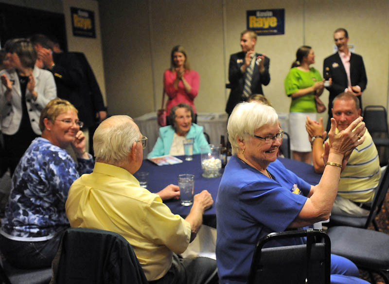Staff photo by Michael G. Seamans Suppoerters cheer for Kevin Raye, candidate for US second congressional district, as poll numbers roll in at the Ramada Inn in Bangor Tuesday night.