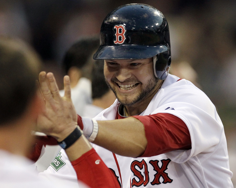 Boston Red Sox's Cody Ross is congratulated at the dugout after hitting a solo homer in the fourth inning against the Miami Marlins at Fenway Park in Boston tonight.