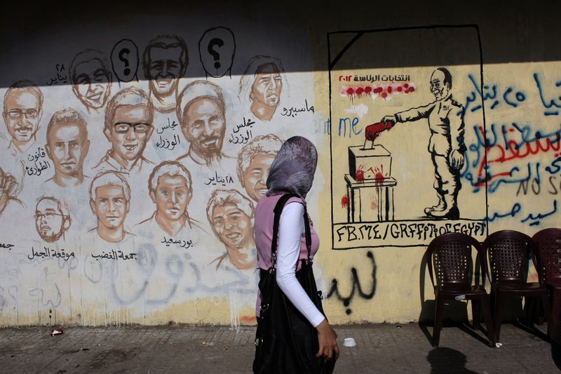 An Egyptian woman passes by a wall with graffiti depicting Egyptians killed during the revolution, left, and the military council casting a vote with a blooded hand and Arabic that reads