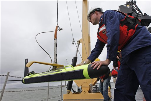 Lt. Sam Greenaway moves a new side scanning sonar unit into position aboard the Ferdinand R. Hassler.