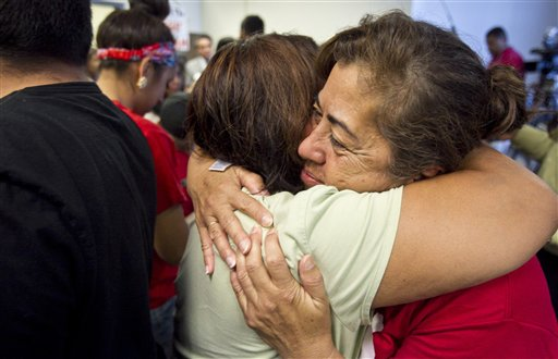 Rosa Maria Soto hugs Eva Monteloneo, left, after hearing President Obama is easing enforcement of immigration laws today in Phoenix.