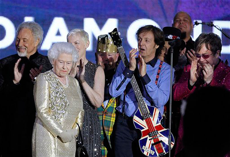 In this Monday, June 4, 2012 file photo, Britain's Queen Elizabeth II, 2nd from left, is joined on stage by performers Sir Tom Jones, Annie Lennox, Sir Paul McCartney and Sir Elton John at the conclusion of the Queen's Jubilee Concert in front of Buckingham Palace, London. McCartney turned 70 years of age Monday June 18, 2012. (AP Photo/Joel Ryan)