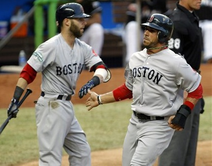 Boston Red Sox's Mike Aviles, right, is congratulated by teammate Dustin Pedroia after scoring on a ground ball by Scott Podsednik against the Miami Marlins in the third inning of today's interleague baseball game in Miami.