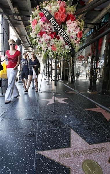 Pedestrians walk past flowers placed on the Hollywood Walk of Fame star for actress Ann Rutherford, who died in Beverly Hills on Monday, in the Hollywood section of Los Angeles Tuesday, June 12, 2012. Rutherford, the demure brunette actress who played the sweetheart in the long-running Andy Hardy series and Scarlett O'Hara's youngest sister in