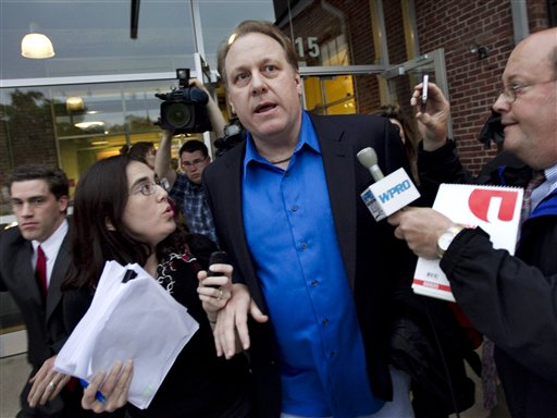 In this May 21, 2012, photo, former Boston Red Sox pitcher Curt Schilling, center, is followed by members of the media as he departs the Rhode Island Economic Development Corporation headquarters in Providence, R.I.