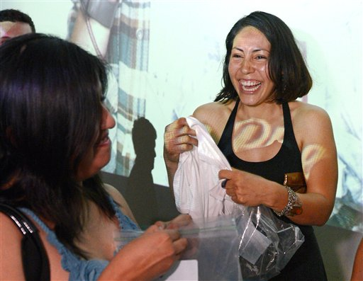 Karen Arellano, right, smells shirts with her friend Christina Lopez during a pheromone party recently in Los Angeles.