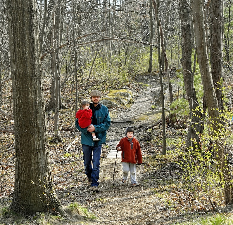 "Neighborhood resident Tim Willoughby walks one of the paths in ""Canco Woods,"" with daughter, Maeve, 2, and son Thomas, 4, in April."