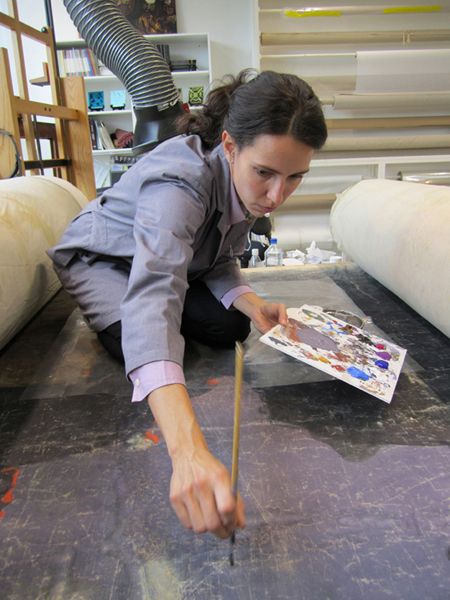 A Williamstown Art Conservation Center conservator touches up scenes from a 161-year-old panorama of Pilgrim's Progress. Flasche Vinylic colors were used for the touch-up work as they dry matte to match the original finish. The restored panorama, property of the Saco Museum, will be exhibited from June 30 to Nov. 10 at venues in Biddeford and Saco.