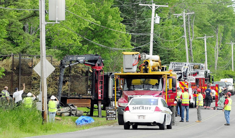 Investigators look over the logging truck where a man was electrocuted Friday afternoon on Spears Corner Road in West Gardiner.