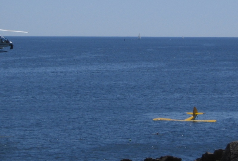A witness to the plane crash took this photo shortly after the plane hit the water. The pilot can be seen in the water in front of the plane. The front of the helicopter that helped is visible at the far left.