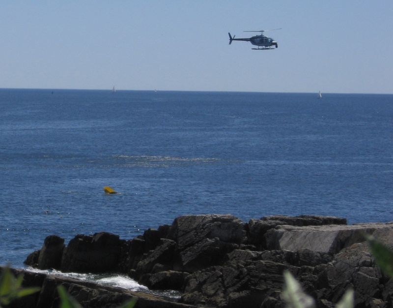 The helicopter circles as the plane sinks.