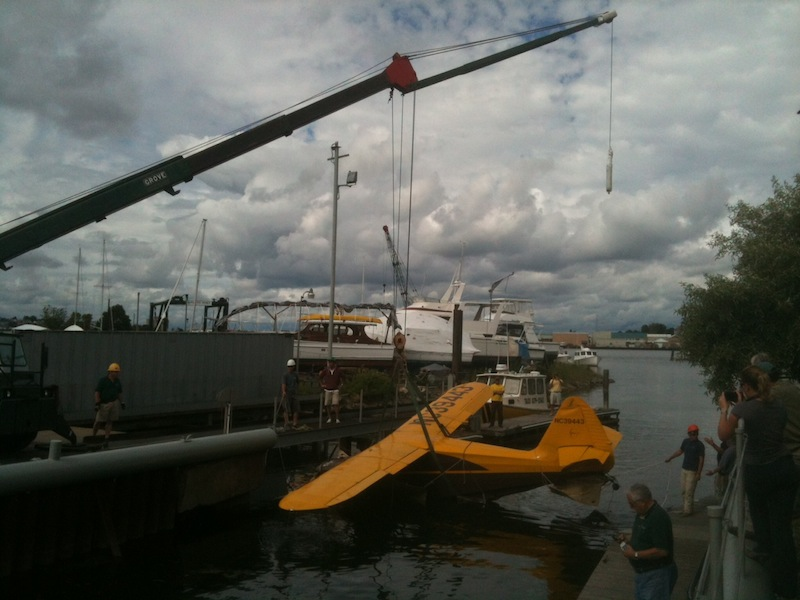 The Stinson plane involved in Sunday's fatal crash at Fort Williams Park is lifted onto the dock at South Port Marine in South Portland on Tuesday, June 26, 2012.