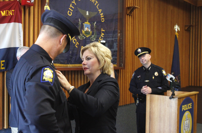 Cindy Rogers pins a badge on her husband Gary Rogers during a ceremony today at the Portland Police Department at which six officers were promoted. Rogers, who has 24 years of experience, was promoted to commander, the third highest ranking position at the department.