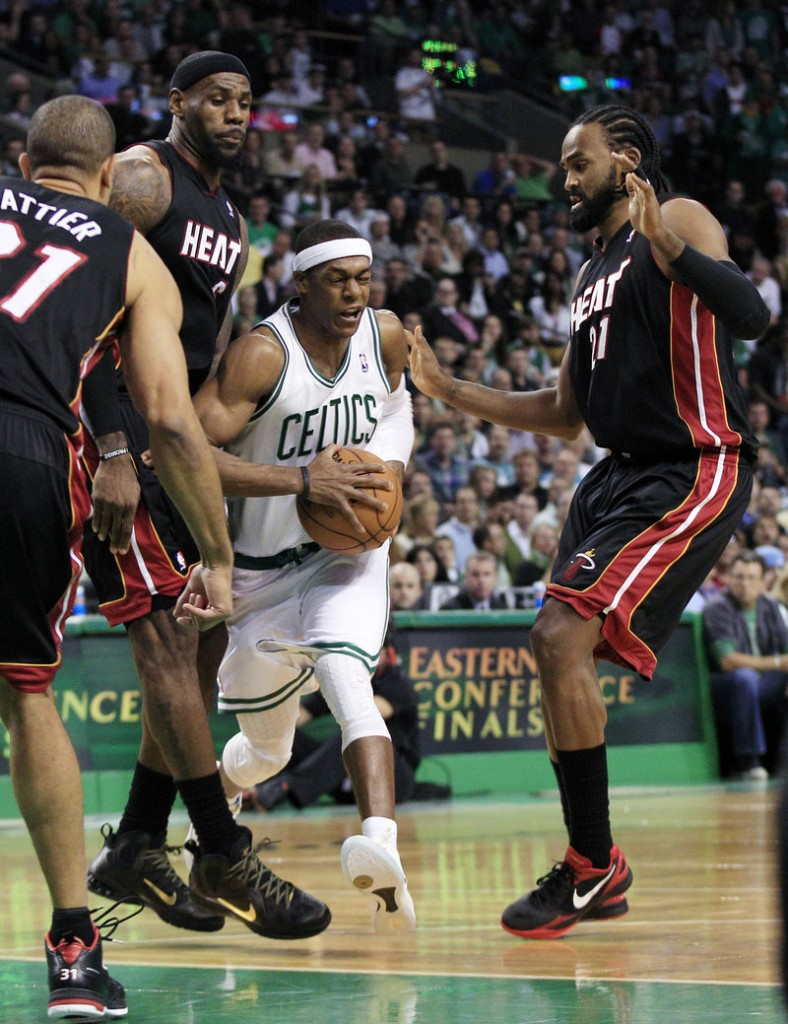 Rajon Rondo of the Boston Celtics threads his way through the Miami defense Friday night, including, left to right, Shane Battier, LeBron James and Ronny Turiaf.