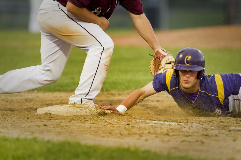 Nick Melville of Cheverus dives back to first base ahead of the tag by Windham's Robbie Hamilton. Cheverus claimed the Telegram League baseball title with a pair of wins Friday – 3-2 over Marshwood in eight innings, and 10-8 over Windham.
