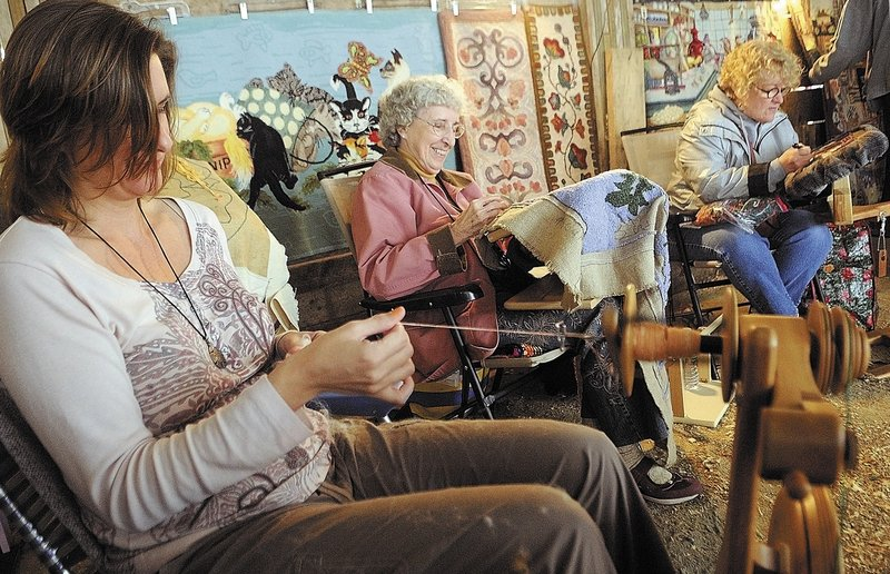 Becky Foster, left, of Harrison spins yarn as Vivian Morissette of Pittston and Julie Stewart of Litchfield hook rugs during the Fiber Frolic Fair on Saturday at the Windsor Fairgrounds. The fair continues through today. The fairgrounds are located on Route 32 between routes 17 and 105.