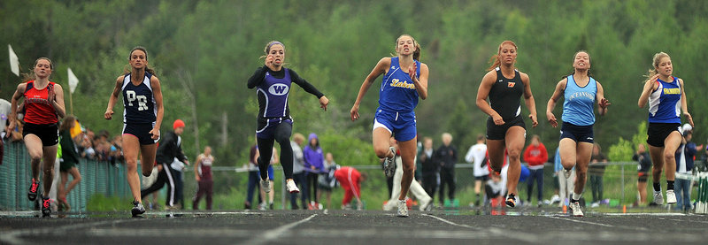 Katie Hall, center, of Lake Region storms to the finish to win the 100 in a Class B record 12.33 seconds. Hall, a freshman, also captured the 200 and the long jump at the Class B state meet.