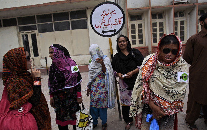 Pakistani Allah Rakhi, 51, third from left, whose nose was sliced off by her husband, stands with acid-attack survivors outside a hospital in Rawalpindi on May 20.