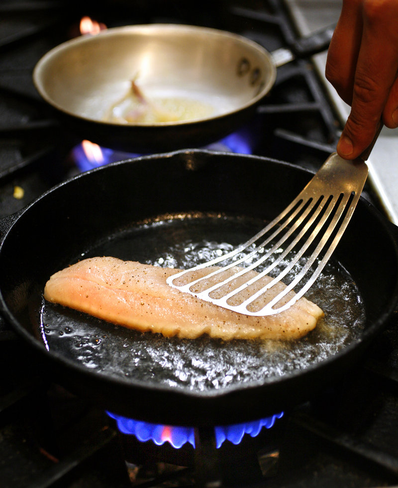Executive chef Peter Sueltenfuss of Grace prepares his pan-roasted red fish.