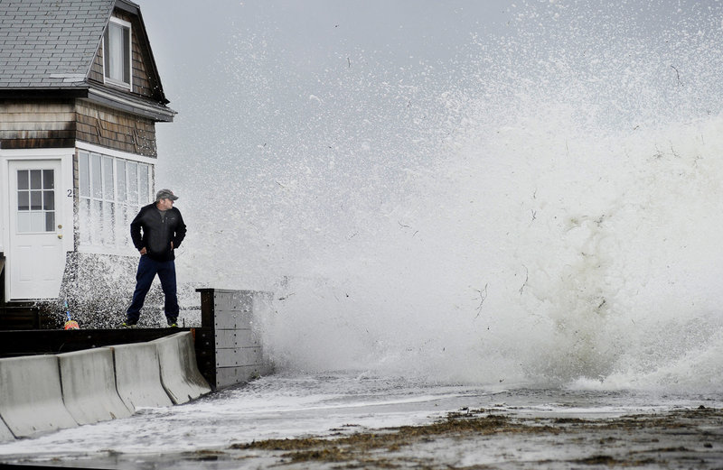 Bernie Malouin watches a large wave crash over Eastern Avenue at Camp Ellis in Saco from a wall in front of his cottage Monday.