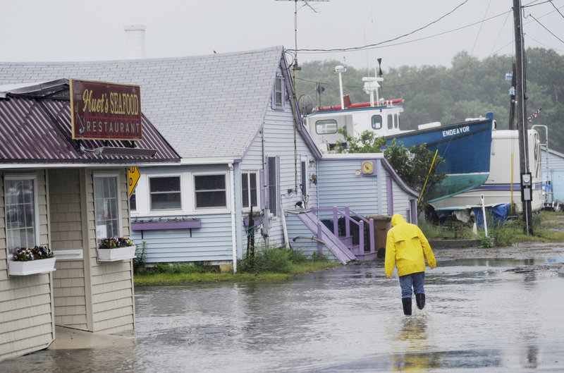 Michael Clair of Biddeford walks down a flooded Bay Avenue in front of Huot's Restaurant at Camp Ellis in Saco on Monday. Saco got just over 6 inches of rain in three days.