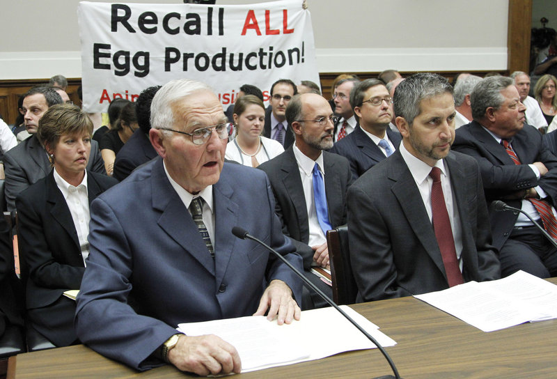 "Protesters unfurl a banner as Iowa egg farm owner Austin ""Jack"" DeCoster, left, testifies in 2010 at a House subcommittee hearing on an outbreak of salmonella in eggs. DeCoster previously owned an egg farm in Maine that had a reputation as a harsh workplace."